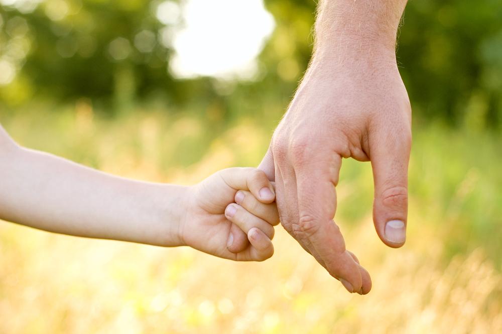 child hold man's finger
